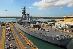 The battleship EX-USS Missouri (BB 63) is being undocked by Pearl Harbor Naval Shipyard workers to begin its 2-mile journey back to Ford Island.