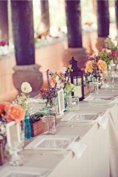 White table cloth, Mason jars & wild flowers make a stylish yet inexpensive table setting.