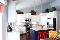 Liberty Homes | Sierra floor plan  Model home in West Jordan, UT  U-shaped kitchen, island bar, granite countertops, white cabinets, dark wood island bar and red accents