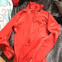 Nike running long sleeve Has thumb holes and warm light material. Tight fitting. Great for running on cold mornings. Red-orange color Nike Tops Tees - Long Sleeve