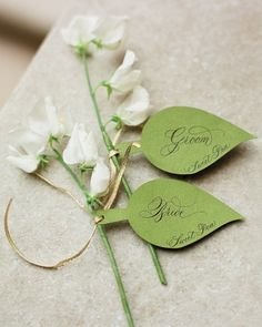 Escort Cards Paper leaves inscribed with guests' names were tied to an array of different flower stems. See More Escort Cards Wedding Seating Cards, Wedding Place Cards, Cheap Wedding Flowers, Flower Bouquet Wedding, Wedding Garlands, Bridal Bouquets, Paper Leaves, Paper Flowers, Faux Flowers