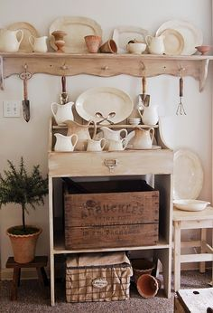 awesome display of white accessories... especially like the large plate rack with the garden utensils