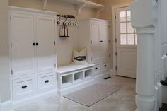Cottage mudroom boasts a long wall-to-wall shelf accented with corbels suspended over white cabinets accented with oil-rubbed bronze hardware flanking built-in bench with shoe cubbies with whale pillow placed under a row of hooks mounted on a beadboard backsplash alongside diamond pattern tiled floor.