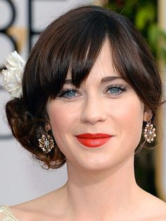 Updo on Zooey Deschanel.   Recreate the look by working mousse into damp hair and blow-drying with a round brush. Sweep hair into a low ponytail behind one ear, leaving bangs or wispy front layers loose, and secure with an elastic. Tease sections of ponytail and wrap into a loose bun; pin to secure and set with hairspray.  I will omit the flower!