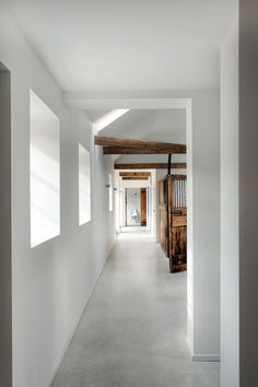 Corridor in a renovated stable by AR Design Studio. I like the cement floor and bold contrasts between old and new.