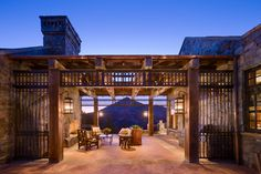 An outdoor porch in between the main house and garage in this Montana Log home designed by Locati
