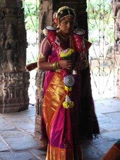Tamil bride -  The bride, with help of her female relatives, dresses a nine yard sari. When done she returns to the mandapa. A sack of paddy is put on the floor. Bride's father sits on the sack. The bride sits on his lap. This sack is a symbol of good luck and both material and spiritual abundance.