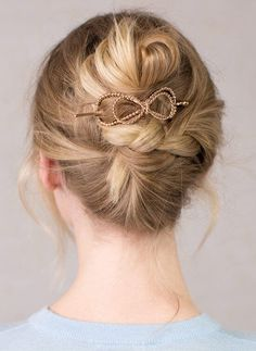 Updo in which the begins in a French twist, continues as a braid, and ends as a small bun topped off with a golden bow-shaped barrette