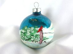 Give your tree a handmade look with this vintage Christmas ornament! The blue ornament sports a hand painted cardinal sitting on a fence post in