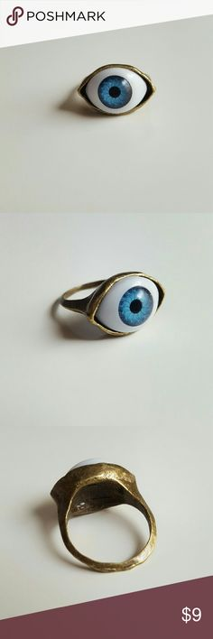 """Blue Eyed Ring This lovely antiqued bronze ring has a lovely blue eye with black pupile and detailed lines of gold snd green in the iris. The eye measures 1"""" across and 1/2"""" wide. Brand new and unused this is a size 6 and is great with your favorite shirt and jeans. Other great eye themed jewlery listed in my closet. Jewelry Rings"""