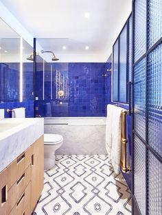 Bright bathroom with marble, printed blue tile, and contrasting blue backsplash