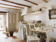Cocina de estilo rústico con mobiliario diseñado a medida en color verde y alacena con frentes acristalados y visillo.