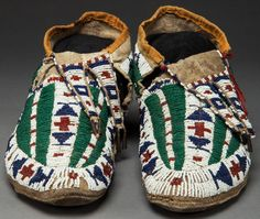 A PAIR OF SIOUX BEADED HIDE MOCCASINS  c. 1890  sinew sewn and lane-stitched in various shades of opaque and translucent glass seed beads, each with a band enclosing small geometric motifs down the vamp and encircling the foot, rawhide soles