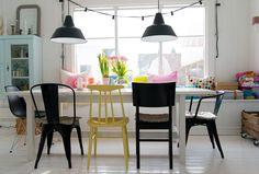 Guirlande lumineuse noire autour de la fenêtre + chaises de différentes couleurs sur table blanche