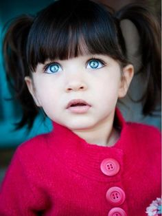dark hair and blue eyes! This little girl is beautiful!!