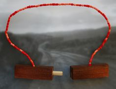 RACHEL BELL-NZ  'Post'  Post Necklace,  May 2012  $225  Cotton, plastic, wood (Australian hardwood and pine). Red/orange beads  In 'Post' I am utilising materials that I associate with my rural background (including rabbit, knitting needles, linen, gorse and willow), considering notions of home and place while investigating further the combination of natural and traditionally precious materials in a jewellery format.""