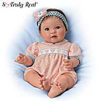 So Truly Real® baby doll by Ping Lau is handcrafted of RealTouch® vinyl, poseable, and weighted for realism. Pink polka-dot heart romper.