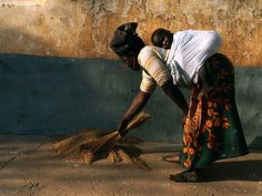 Nigeria Photography | With her child safely bundled, a Nigerian mother threshes wheat grain.