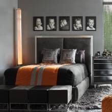 This boy's room has a platform bed with Harley-Davidson motorcycle-themed bedding, a tool chest-cum-nightstand, and chain-link metal mesh draperies reflect the youngster's interests.