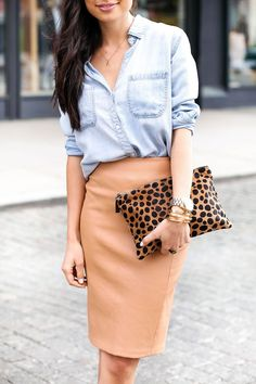 Shop this look on Lookastic: https://lookastic.com/women/looks/denim-shirt-pencil-skirt-clutch-bracelet-watch/10675 — Light Blue Denim Shirt — Tan Leather Pencil Skirt — Gold Bracelet — Gold Watch — Tan Leopard Suede Clutch