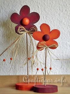- patterns below  - 1 cm plywood for the flowers  - 1.8 cm plywood for the base  - 2 x 4mm wide wooden sticks each 2 different lengths  - 2 halves of 3 cm wooden balls  - 2 halves of 2 cm wooden balls  - pencil  - tracing paper  - saw  - acrylic paint in red, brown, and orange  - natural raffia  - 8 x 6mm orange wooden beads  - hot glue gun  - drill with 4mm bit  - wood glue