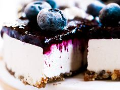 Healthy paleo blueberry yogurt cheesecake recipe. Incredibly creamy and satisfying! Filled with a tangy and sweet creamy yogurt filling.
