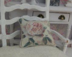 A single dollhouse miniature cushion in scale 1:12