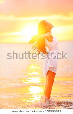 Free woman enjoying freedom feeling happy at beach at sunset. Beautiful serene relaxing woman in pure happiness and elated enjoyment with arms raised outstretched up. Asian Caucasian female model. - stock photo