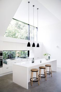 Kitchen Ideas - In this modern kitchen, three black pendant lights above the island draw the eye upwards to highlight the double-height ceiling, while the white cabinets help the kitchen blend into the white walls. #KitchenDesign #KitchenIdeas #WhiteKitchen