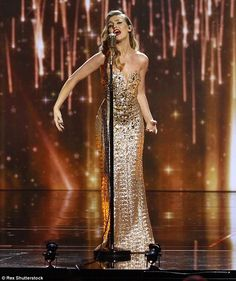 Going for gold: Perrie, 22, was the picture of elegance in her floor-length frock which ac...