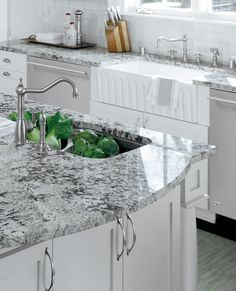 White cabinets and a farmhouse sink with black and white granite countertops.