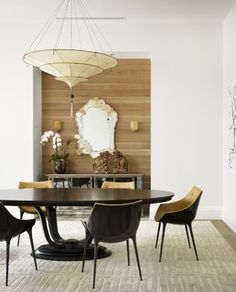 gorgeous leather and acrylic/lucite (?) dining chairs in a white dining room with wood accent nook.
