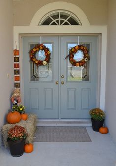 Pumpkins, mums and haystacks warm up an entryway for fall.