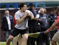 Stanford quarterback Andrew Luck passes a pro scouts watch in background during Stanford football Pro Day on the Stanford University campus in Stanford, Calif., Thursday, March 22, 2012. (AP Photo/Paul Sakuma)