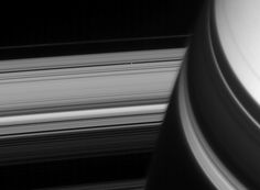 Pan, a small ring-embedded moon (28 km/17 mi wide) coasts into view from behind Saturn. The view of the rings is distorted near Saturn by the planet's upper atmosphere. The view was acquired at a distance of approximately 1.8 million km (1.1 million mi) from Pan. Image scale is 11 km (7 mi) per pixel on Pan.