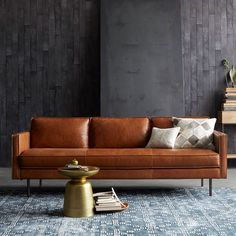 This moody grey colour scheme is contrasted by the warmth of brown leather and a brass side table.