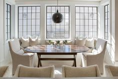 Chic dining room features a black pierced Moroccan lantern illuminating a built-in window seat dining banquette facing an oval wood x based dining table lined with natural linen swoop arm dining chairs.