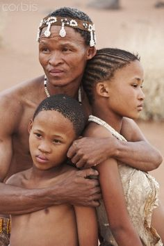 Africa |  San (Bushmen) father hugging his children. Botswana.