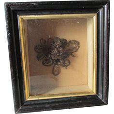 A nice antique (circa 1860-70s) Victorian hair wreath or bouquet.  The Hair Bouquet is in the original shadowbox frame and is complete with old glass