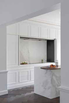 Parisian/French-style 'hide away' kitchen with white classic traditional concealed storage cupboards with mouldings/panelling, dark herringbone timber floor, Calcutta marble benchtops and splashback, island bench with waterfall edges
