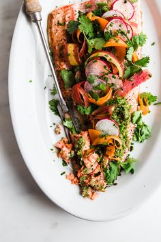Roasted Salmon with Spring Pesto - think peas, mint, pistachios, and carrot tops, all blending together to make one vibrant and earthy pesto— that's what is spooned on this roasted salmon and just like that dinner is done! : The Modern Proper