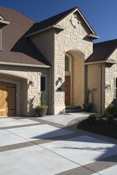 A gorgeous stone home exterior with a wood garage door and stained wood front door. The paved driveway and archway over the door create a welcoming and elegant entryway. See how much it costs to pave a driveway.