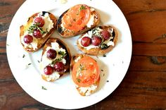 Two bruschettas - roasted tomato and goat cheese & roasted grapes with ricotta and honey drizzle. Both look great!