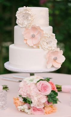Sweet, small wedding cake in white with sugar flowers and satin ribbon.