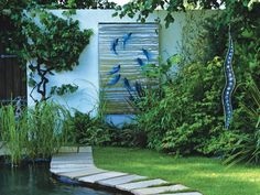 An outdoor wall is used to display an artwork featuring leaping fish, which, along with a sculpture of peas in a pod, adds depth and drama to this garden area. The whimsical space also features ornamental grasses and shrubs growing near a paver tile walkway.