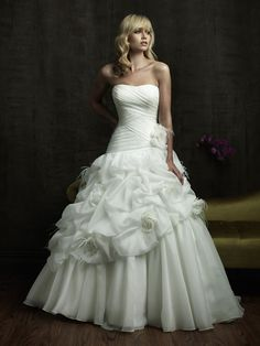 Romantic ball gown with a strapless ruched bodice The lovely caught up skirt is accented with feathers flowers Fabric Satina and Organza