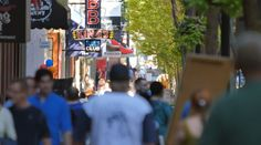 Stock video footage The scene on 2nd Avenue in Nashville, Tennessee as crowds of people walk up and down the street near BB Kings historic place on a bright sunny day with green trees on the sidewalk ...
