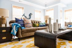 """This living room was just really weighed down,"" says interior designer Jennifer Walter. Between the dark brick-red accent wall and her client's existing heavy sofa and chair, she knew she had to lighten things up. Also, a long wall was a mishmash of media, leaning shelves and other disparate pieces that didn't stand up to the wall's large scale. Major parts of the new design are built-in cabinets and shelves that Walter drew on a napkin while on vacation. Her coastal surroundings at the..."