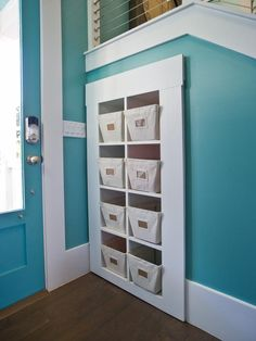 A built-in storage unit offers cubbies to stow shoes and outdoor apparel. The mobile unit pulls out to reveal the homes electronic system, tucked discreetly under the stairwell.