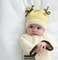 On fond pour ce bonnet vraiment original, avec ses cordelières à nouer de chaque côté ! Tricoté en ' laine partner 3.5 ', coloris Ecru, Soufre et Sapin.Modèle N°19 du catalogue N°129 : Automne/hiver 2015, Layette Facile.